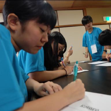 勉強に向かってノートに書き込むキャンプ参加者